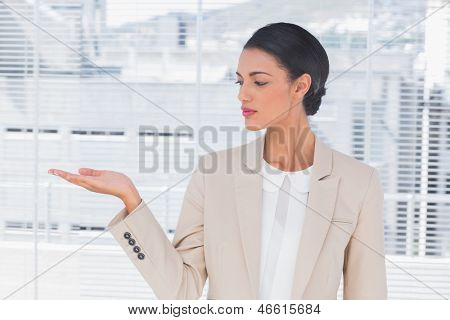 Attractive businesswoman opening her hand in a bright office