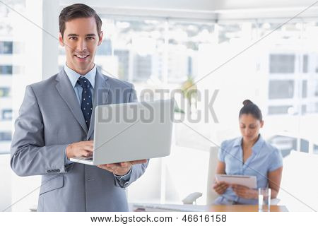 Businessman using laptop standing in office smiling at camera with woman working behind him