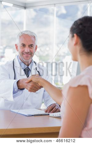 Patient shaking hands to doctor in the office at desk