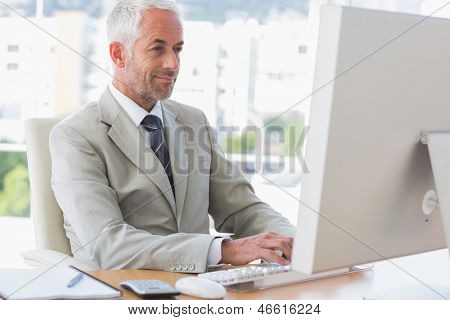 Happy businessman working on computer at his desk