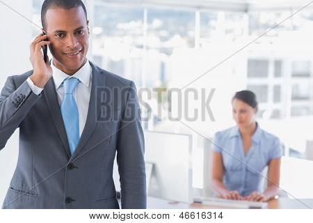 Happy businessman on a call with woman working at desk behind