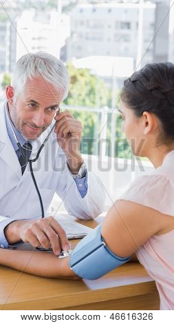 Doctor measuring the blood pressure of his patient in the office