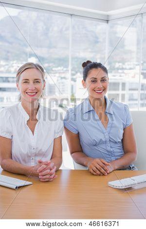 Happy businesswomen sitting side by side at desk in office