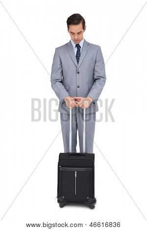 Serious young businessman waiting with his suitcase on white background