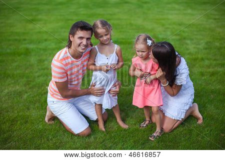 Portrait Young Family Of Four Sit On The Grass And Have Fun