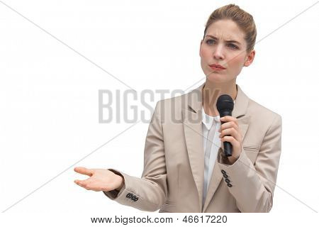 Frowning businesswoman holding microphone on white background