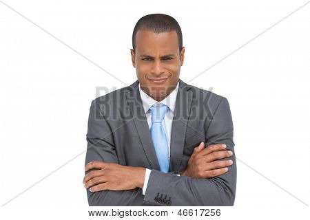 Doubtful businessman with arms crossed on white background