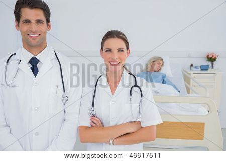 Two doctors smiling and standing in front of a hospitalized patient