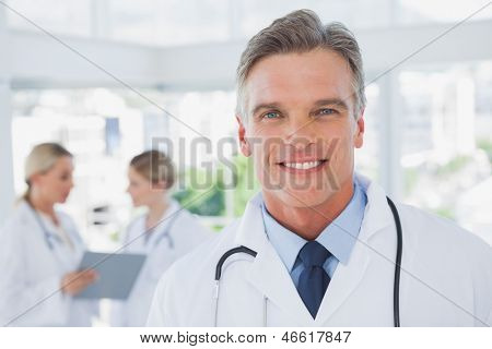 Smiling grey haired doctor standing in his office with colleagues working behind