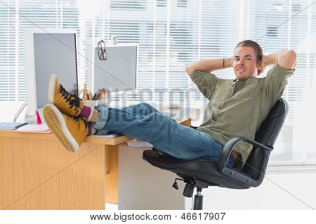 Designer relaxing with foot on the desk in a modern office