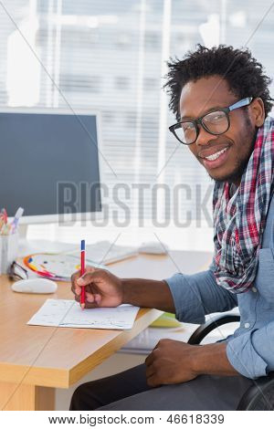 Cheerful designer drawing something with a red pencil in a modern office