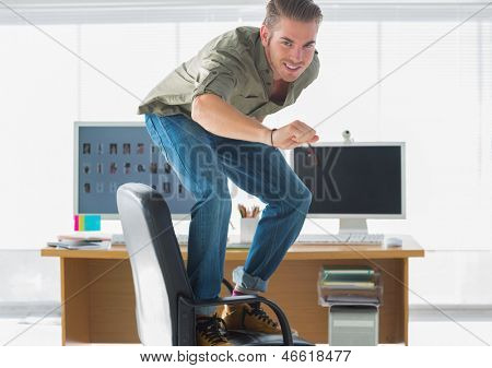 Smiling man surfing his office chair and having fun
