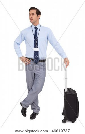 Serious businessman waiting with his suitcase on white background