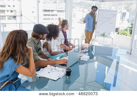 Young designer presenting a flow chart to colleagues during a meeting