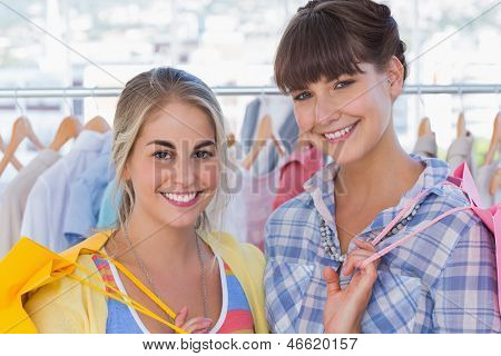Portrait of two cheerful friends doing shopping
