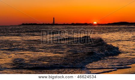 The Cape May Point Lighthouse And Waves On The Atlantic At Sunset, Seen From Cape May, New Jersey.