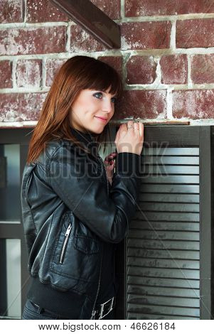 Young woman against a brick wall