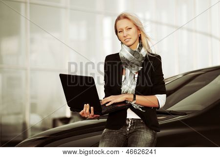 Young business woman with laptop against office windows