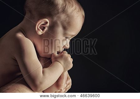 Portrait of beautiful baby. Over black background.