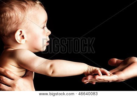 Baby is holding father's hand. Over black background.
