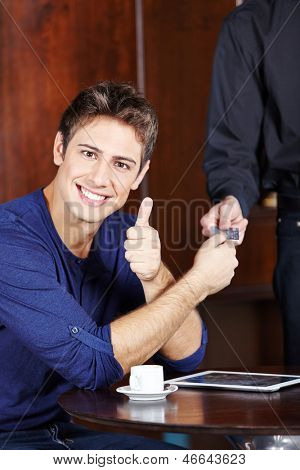 Young man paying with credit card in caf�?�?�?�© and holding his thumb up