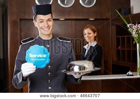 Smiling concierge in hotel reception holding service sign