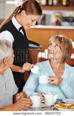 Waiter serving senior woman milk to coffee in coffee shop