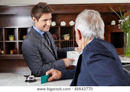 Senior guest in hotel asking receptionist for the way