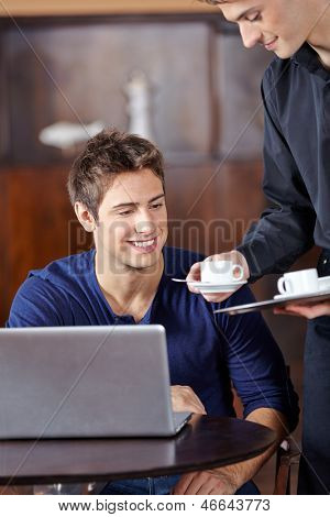 Waiter in caf�?�?�?�© serving man a hot cup of coffee