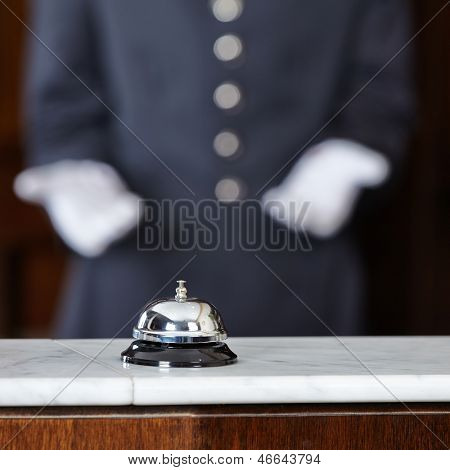 Concierge with white gloves pointing to hotel bell on counter