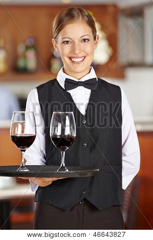 Happy female waiter with two red wine glasses in a restaurant