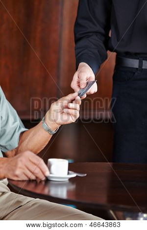 Man paying coffee in caf�?�?�?�© with his credit card