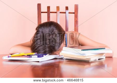 Exhausted student  sleeping with her head on a table and books by her side