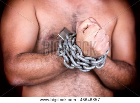 Shirtless man with his hands chained with strong steel chains and a padlock (on a black background)
