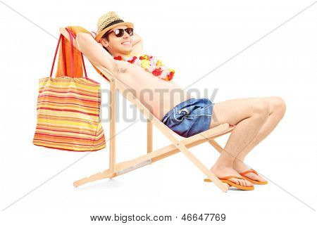 Full length portrait of a man enjoying on a sun lounger, isolated on white background