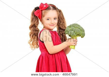 A smiling girl holding a broccoli isolated against white background