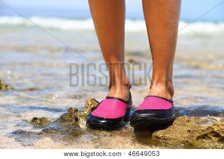 Water shoes / swimming shoe in Pink neoprene on rocks in water on beach. Closeup detail of the feet of a woman wearing bright pink neoprene water shoes standing on rocks at the edge of the ocean.
