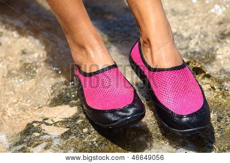 Water shoes / swim shoe in Pink neoprene on rocks in water on beach. Closeup detail of the feet of a woman wearing bright pink neoprene water shoes standing on rocks at the edge of the ocean.
