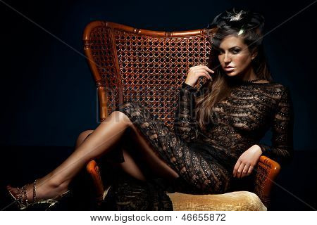 Attractive Elegant Lady Sitting On Chair Wearing Black Sexy Dress.