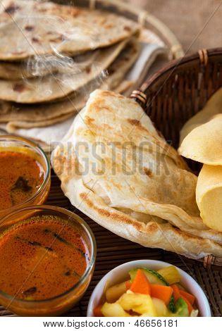 Indian meal, Chapati flatbread, roti canai, dal, curry, teh tarik or pulled tea, acar. Famous indian food.