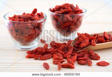 Red dried goji berries, wolfberry or lycium, chinese herbal medicine close-up on bamboo mat.  Lycium barbarum.