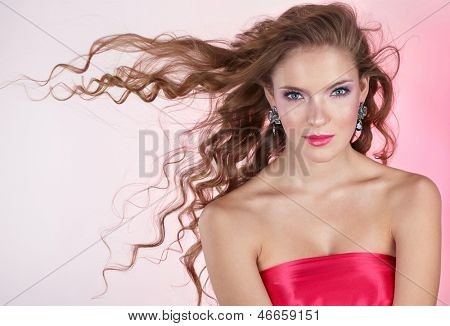 Beautiful young woman with long curly hair on pink background