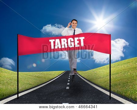 Young smiling businessman running on a road in the middle of green area with a banner with target written on it