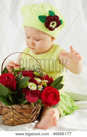 Portrait of little girl dressed in greenish clothes and hat sitting on bedding with wicker basket of flowers