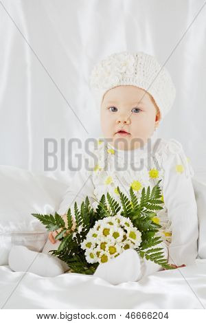 Portrait of little girl in white clothes, who sits on white coverlet between pillows with bunch of flowers