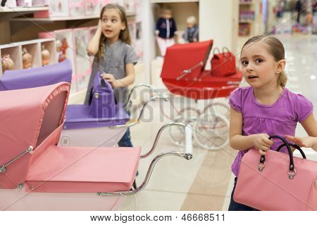 Two girls in a toy store with a rows of dolls purchased a buggy and handbag