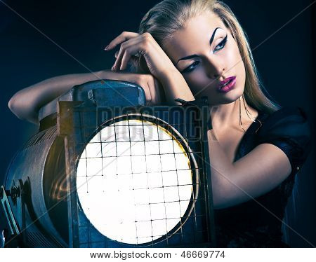 Sexy young woman with old floodlight