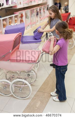 Two girls in a toy store with a rows of dolls purchased a handbag and buggy