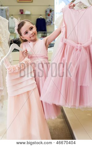 Beautiful girl tries on a pink dress in a store children clothes
