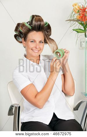 Portrait of mid adult female client removing curlers at parlor